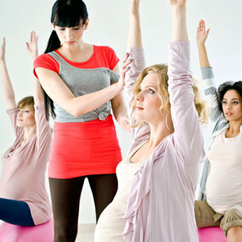 Pregnant women exercise on gym balls with their physical trainer.