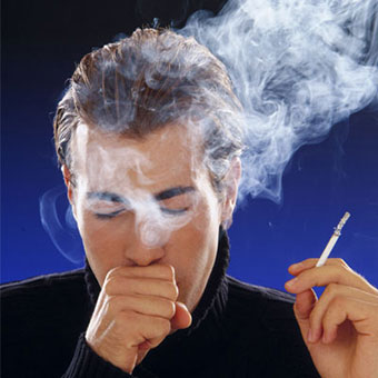 A man coughs while smoking.