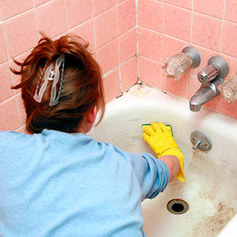 A woman cleans a moldy bath tub.