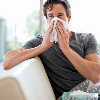 A man with allergies blows his nose into a tissue.