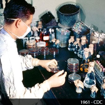 A 1961 technologist works in a lab and examines petri dishes.