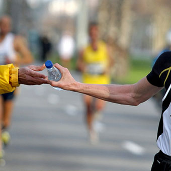 A runner takes a bottle of water during a race.