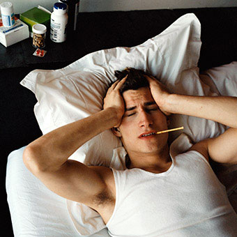 A man in bed with a fever sweating.