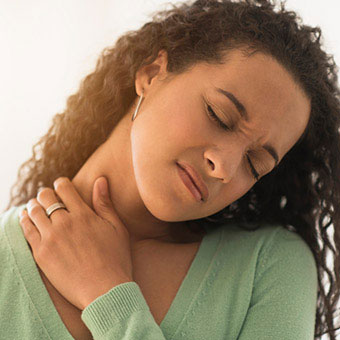 A woman rubs her sore neck due to a pinched nerve.