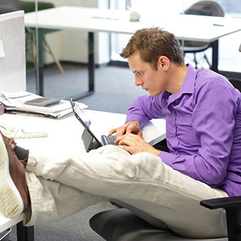 A male worker with poor sitting posture works on his computer at his desk.