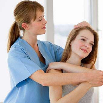 A physical therapist works on the neck and shoulder of a patient with a pinched nerve.