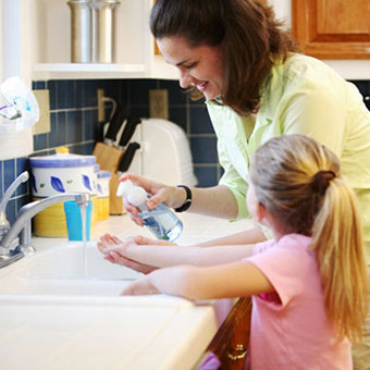 A mother and daughter wash their hands.