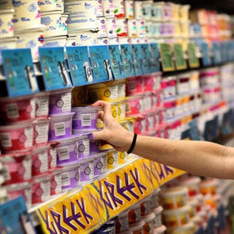 A person shops for yogurt at a supermarket.