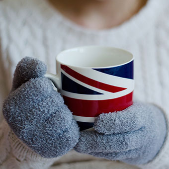 A woman keeps warm by wearing gloves, a sweater, and drinking tea while indoors to keep her Raynaud's phenomenon at a minimum.