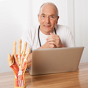 A doctor in his office with a model of a hand.