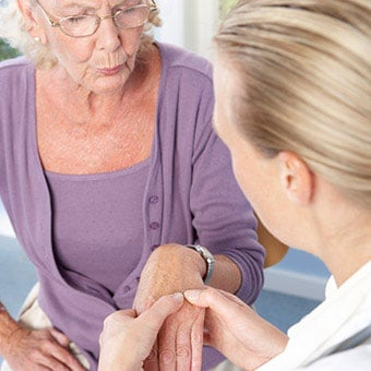 A patient feels joint tenderness as a doctor examines her hand for rheumatoid arthritis (RA).