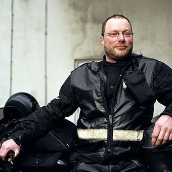 A man with rosacea poses with a motorcycle.