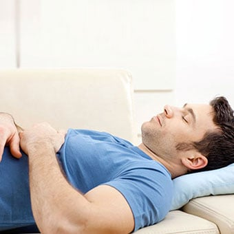 A man rests his back by laying down on the couch.