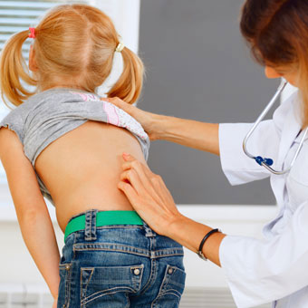 A doctor performs a scoliosis screening on a girl at school.