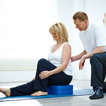 A physical therapist works with a patient on stretching exercises to help with sacroiliac (SI) joint pain.