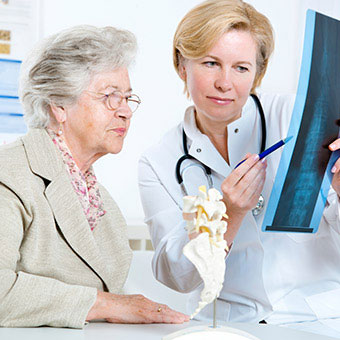 A doctor explains spinal X-ray results to a patient.