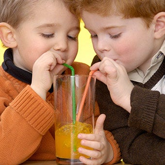 Two boys share a soda.