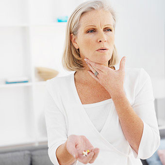 A woman taking medication pills for strep throat.