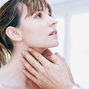 A doctor examining a woman's neck for swollen lymph nodes.