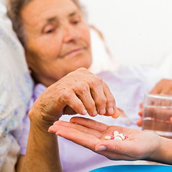 A nurse holds a medication bottle and  explains treatment to patient.