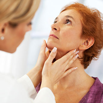 A doctor diagnosing a woman's swollen lymph nodes by examining her neck.