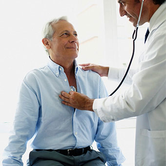 A doctor listens to a patient's chest with a stethoscope.