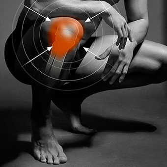 Black and white photo of a man with knee pain highlighted in red.