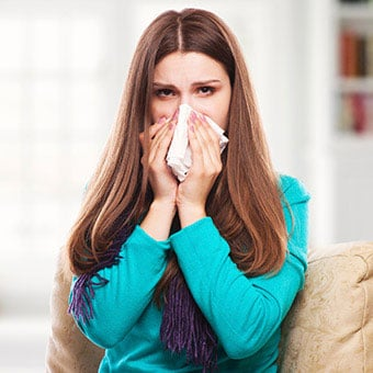 A woman with an upper respiratory infection sneezing into a tissue