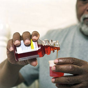 A man take cough medication (antitussives) to reduce the cough of his upper respiratory infection.