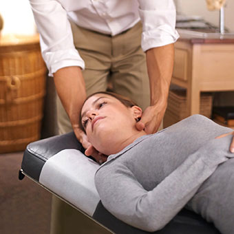 A physical therapist helps a patient with head exercises to treat vertigo.