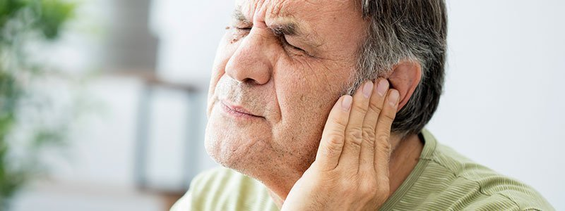 Man with an ear infection holding his ear.