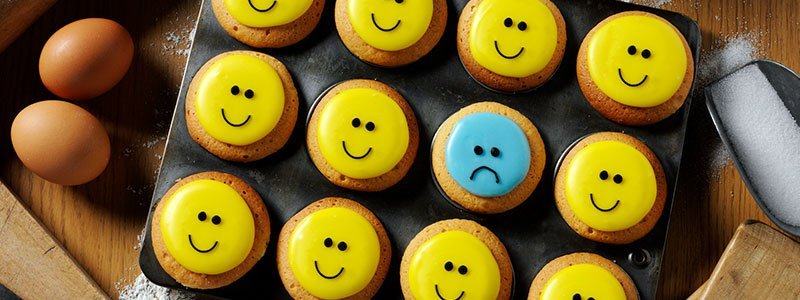 Smiling and frowning-faced cookies on a baking sheet.