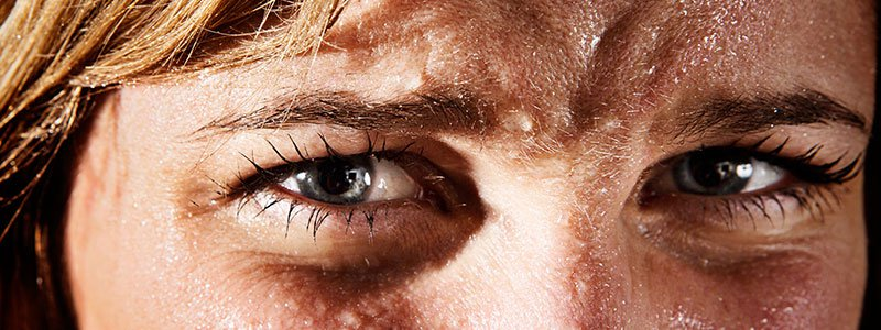 A businessman wipes sweat off his face.