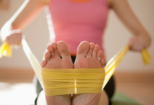 A woman works out with resistance bands at home.