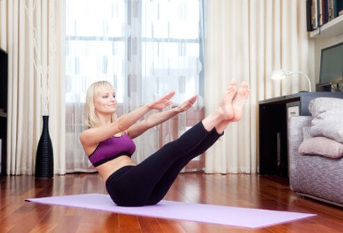A woman performs exercises on a yoga mat at home.