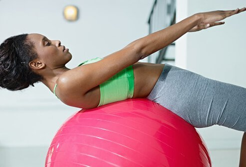 A woman works out with a stability ball at home.