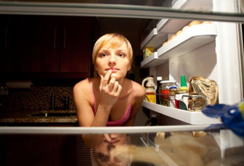 A woman looks in her refrigerator for a late-night snack.