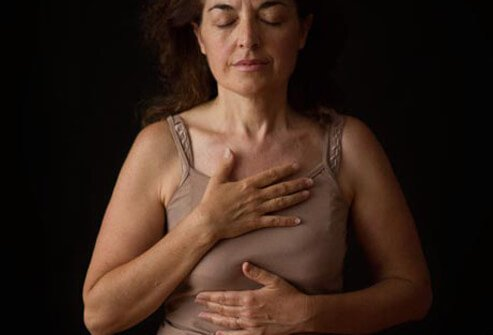 Photo of woman touching chest.
