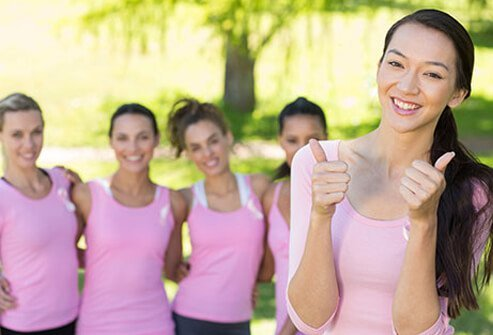A group of young woman wearing pink ribbons show their breast cancer support.