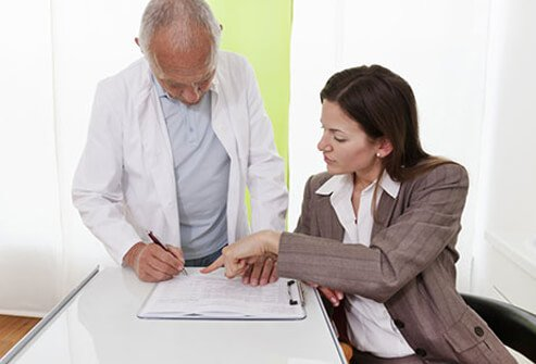 A female patient explains her medical history to a doctor.