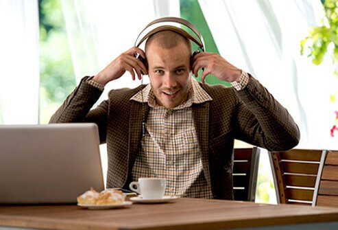 A man puts on headphones to relax and listen to music.