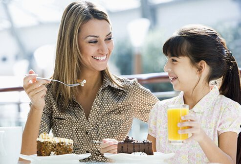 A mother and daughter eat cake.