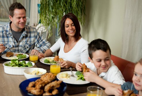 A family eats dinner together at the table.