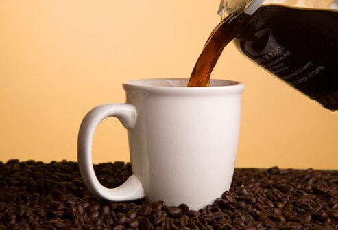 Pouring black coffee into a cup.