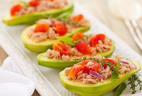 Photo of avocados stuffed with fish and vegetables.