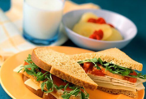 A sandwich with a glass of milk and bowl of fruit.