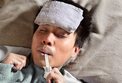 A man with a thermometer in his mouth suffers from a fever.