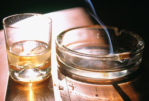 Photo of alcohol and burning cigarette.