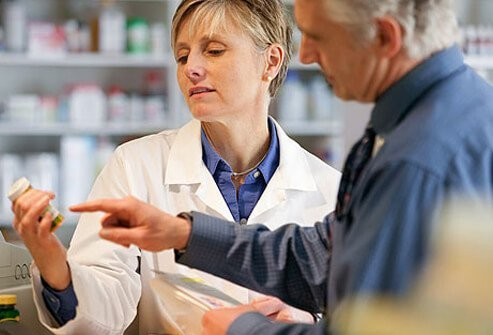 Photo of man reviewing medications with pharmacist.