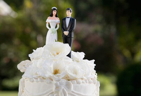 A wedding cake with bride and groom figures on top.